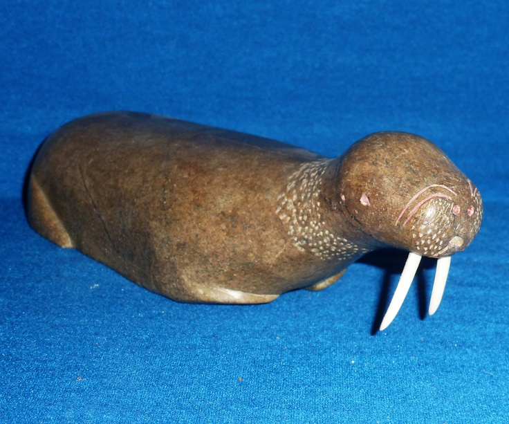 "Item # 	S6095 	Price: 	C$700 Subject: 	Link   Swimming Walrus 	Dated: 	c1960's - Signed Artist: 	Link   Unidentified    		  Community:  	Link   Baffin Island     		  Size: inches/cm 	8"" x 2.75"" x 3"" 20.3 cm x 7 cm x 7.6 cm 		 			 Description: A light tan colored serpentine with green undertones is uncommon for Baffin Island indicating it was taken from a rare vein of stone. Interesting how the unpolished definition of it's facial features hold an odd pink/orange hue."