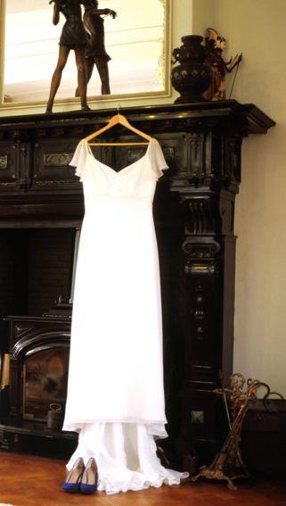Vintage en klassieke trouwfoto van een bruidsjurk aan een hoge schouw in een kasteel kamer.