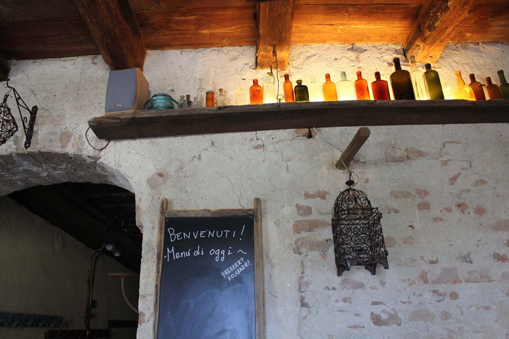 Flasker på en hylde med lys bagved #hylde med lys
