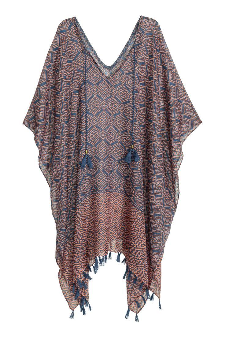 Poncho à motif: Poncho en tissu vaporeux avec motif imprimé. Modèle avec liens à nouer à l'encolure terminés par pompons. Franges à la base. Longueur 86 cm, largeur 100 cm.