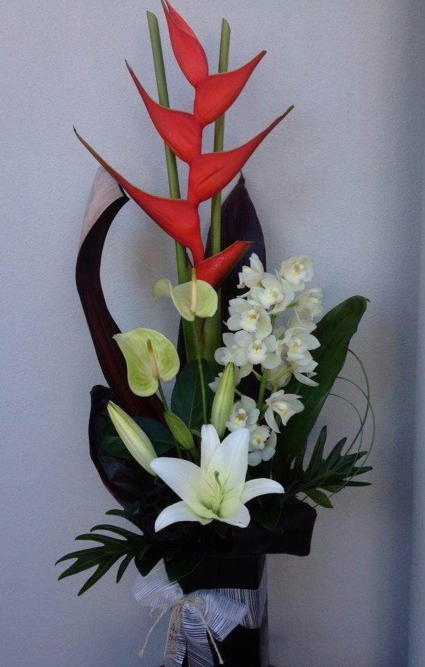 Tropical tall corporate flower arragement with crab claw heliconia, cymbidiums, antheriums and lillies.