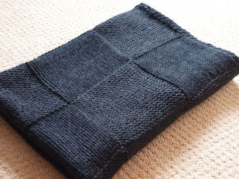 The Stylish Square Blanket. Alternating stocking and reverse stocking stitch squares, the blanket with its seed stitch border is knitted in one piece so that there is no seaming.