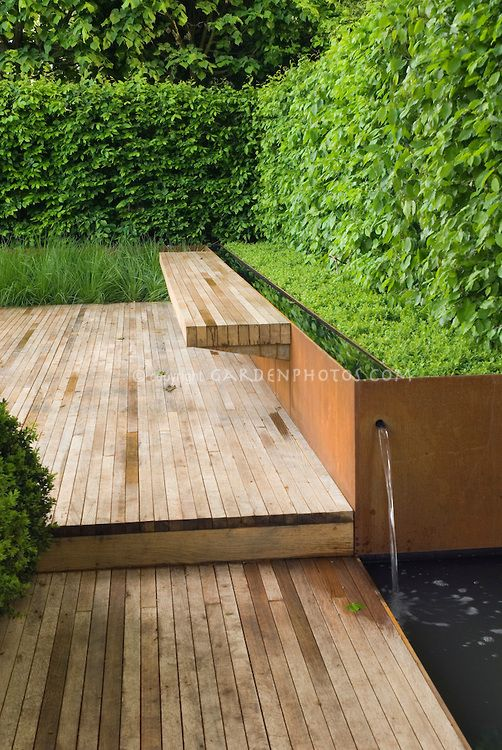 Modern designed deck with garden bench, copper fountain feature and pond, with privacy hedges