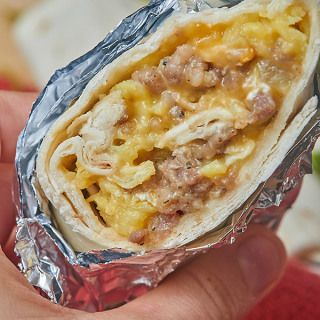These breakfast burritos are so hearty and filling thanks to the sausage, gooey from the cheese, creamy from those perfectly cooked eggs, and you get your veggies in with the bell peppers! I love that you can take it on the go, because it's wrapped in that ammmmazing tortilla! It's a well-rounded breakfast that'll keep going all morning long! www.showmetheyummy.com #breakfast #burrito #scrambledeggs #makeaheadbreakfast #sausage