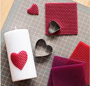 cut heart shapes out of beeswax and adhere to candle!  Clever!