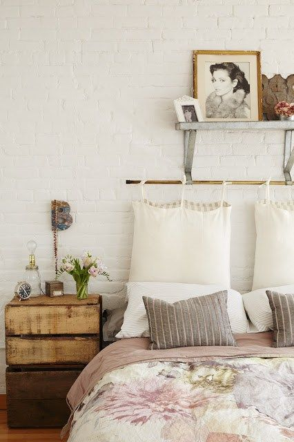 Bedroom of a beautiful loft full of beautiful vintage pieces, creating a really soft rustic and industrial look with large windows creating lots of light and white washed brick walls.