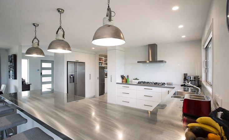 Stunning stainless steel kitchen bench-top with matching pendant lights in a white modern kitchen