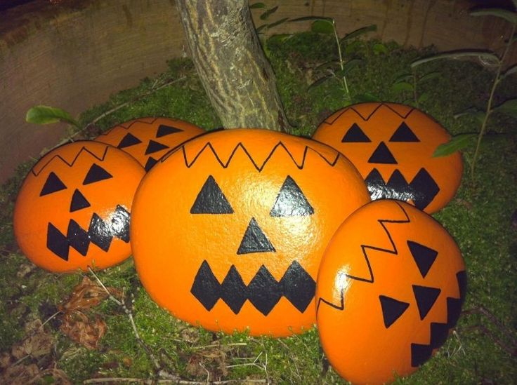 große Steine wie orangenfarbene Halloween Kürbisse bemalt