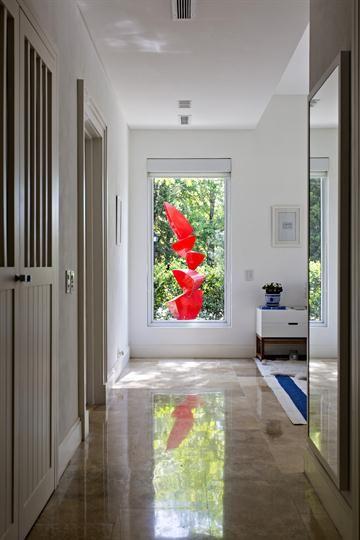 Espacios con inspiración étnica  El  pasillo que comunica a los cuartos deslumbra con su gran longitud, y lo acompaña una alfombra a rayas tejida y varios marcos con fotografías. Al final, a través de la ventana se ve una llamativa escultura roja de Eric Franco situada en el jardín. Foto: Silvio Zuccheri