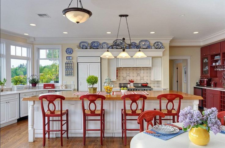 I love everything about this red, white and blue kitchen. White cabinets, red cabinets, red bar stools, blue dishes, light creamy yellow paint, butcher block top island.