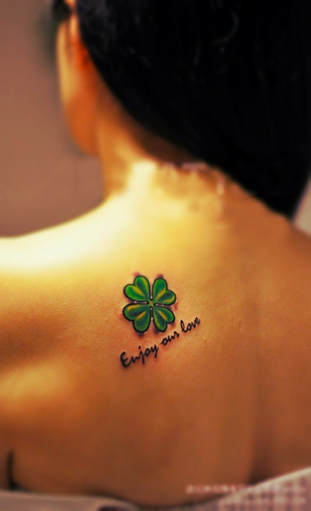 cute bright green four-leaf clover tattoo on the back