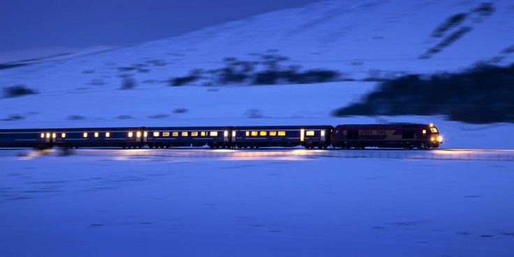 Light glows from the windows of the sleeper as it races through snow covered fields at night