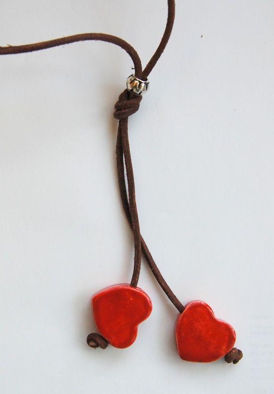 Lange ketting van bruin leren veter met handgemaakte keramiek harten in rood.