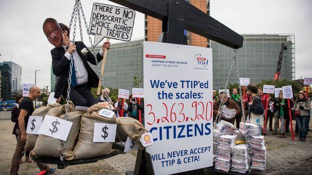 Prall gefüllte Geldsäcke und EU-Kommissionspräsident Jean-Claude Juncker auf der einen, stapelweise Unterschriften auf der anderen Seite: So protestierten Gegner des geplanten Freihandelsabkommens zwischen EU und USA am Mittwoch vor dem Gebäude der EU-Kommission in Brüssel.