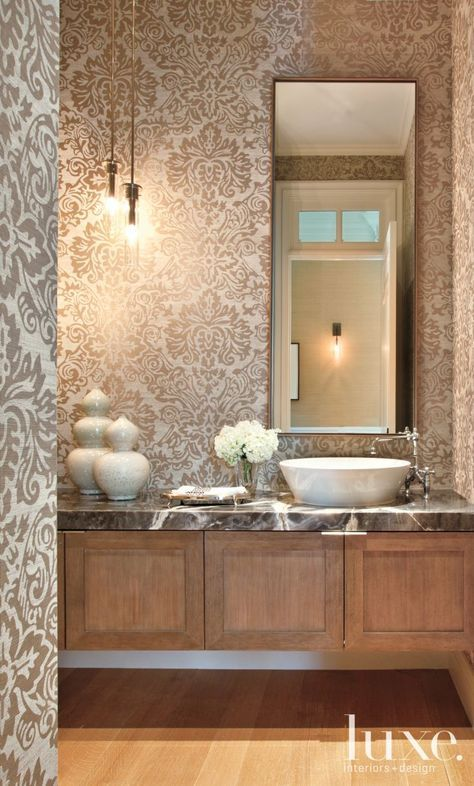 A powder room features an onyx countertop and a printed grass-cloth wallcovering by Phillip Jeffries.