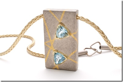 18 carat white gold inlaid with 24 carat yellow gold set with 3 cts of trillion cut aquamarines. The chain and catch are also hand made.
