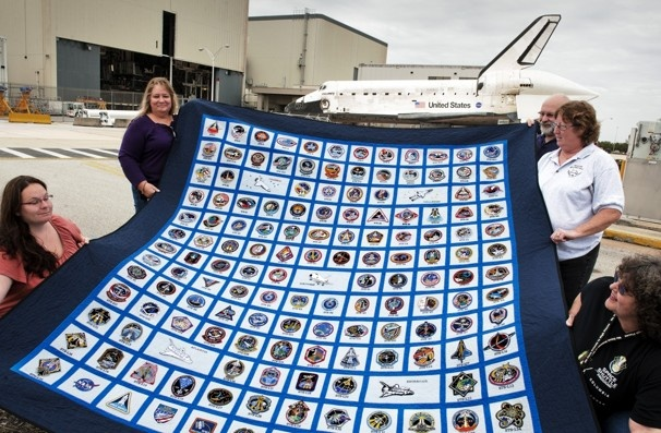 Longtime NASA employees unfurl a quilt made by Vickie Turner, upper right. Turner made the quilt from space shuttle mission patches she started collecting in 1979. Others in the photo are Kim Meyer, lower right, Jamie Crockett, far left, Chuck Hallett, top right, Dena Richmond, top left.  Bill O'Leary / The Washington Post: Spaces Shuttle, Employee Unfurl, Dena Richmond, Longtime Nasa, Mission, Bill O' Leary, Kim Meyers, Jamie Crockett, Chuck Hallette