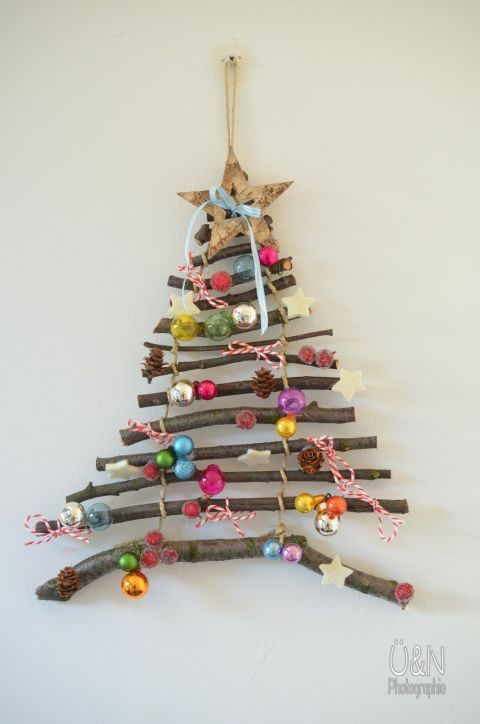 Wood Stick Christmas Tree: Wanna make your Christmas tree this year? Use wood sticks and colorful charms to create this DIY Christmas tree. Hang it along a bare wall to make a fun Christmas statement. Find more easy, rustic, and cool DIY Christmas craft ideas that can decorate your home this Christmas here.