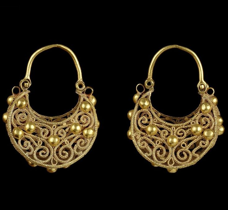 A pair of large Fatimid filigree gold Earrings   Egypt or Syria, 12th Century  of crescent form with flat base and hinged attachment loop, made of filigree and granulations, the base with opposing palmettes containing an arabesque design mounted with hollow hemispheres, the sides with symmetrical arabesque designs also mounted with hemispheres
