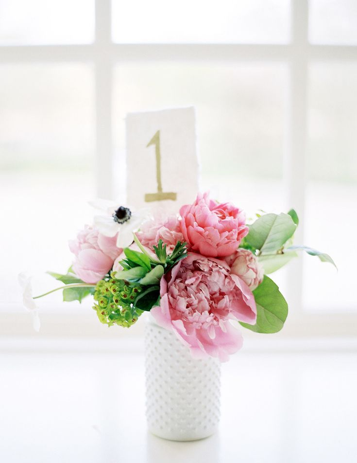 Navy blue and pink beach wedding - pink centerpieces with gold wedding table number