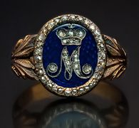 Chased gold, blue guilloche enamel, and rose cut diamond Russian Imperial award ring with cipher of Empress Maria Feodorovna, consort of Emperor Paul I (ruled 1796-1801).  The shoulders of the rings are shaped as laurel leaves.    The diamond set cipher of Empress Maria - 'M' beneath Russian Imperial crown is placed on a royal blue guilloche enamel oval shield.  The enamel is all original and intact.