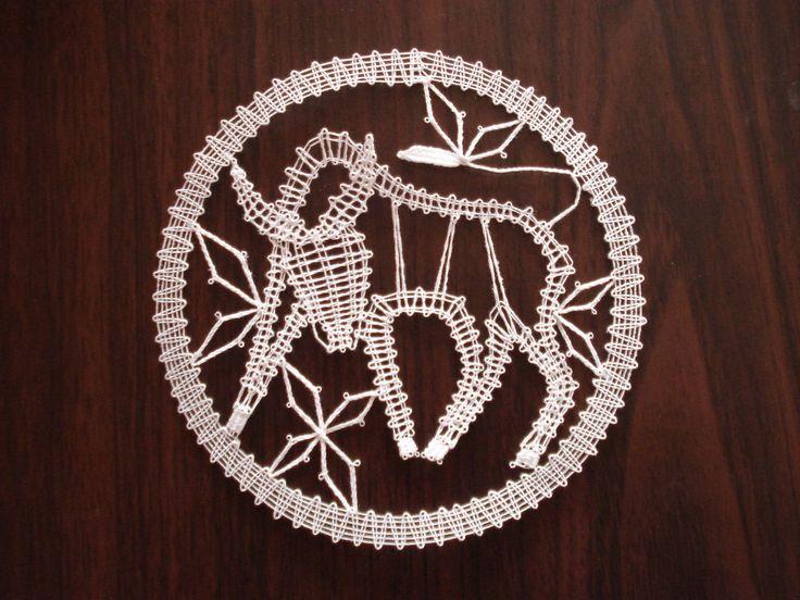 Znamení zvěrokruhu - býk Býk je paličkovaná krajka z bílé kordonetky o průměru 13 cm určená k zarámování či do pasparty.