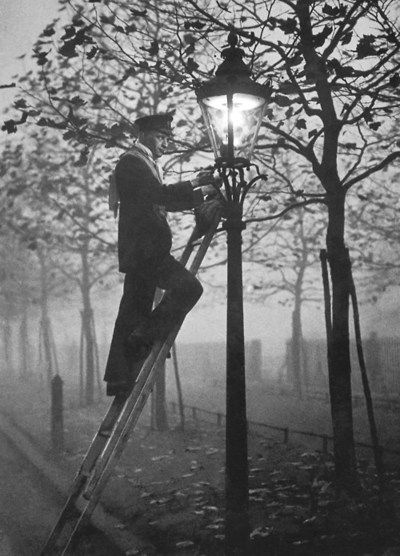 A lamp lighter relighting a gas lamp in the fog on November 17, 1930