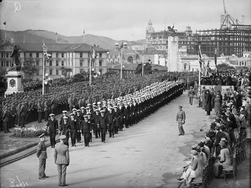 Troops of the Second Echelon of 2NZEF and sailors of the Royal Naval Volunteer Reserve parade at Parliament, Wellington, shortly before their departure in 1940.  Around 140,000 New Zealand personnel served overseas for the Allied war effort, and an additional 100,000 were armed for Home Guard duty.