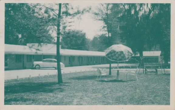 Georgia | Postcard Roundup | Postmarked in 1956, this postcard shows the Orlando Motel in Ludowici, Georgia. On the back:ORLANDO MOTEL on U. S. 301 & 25, 1 mile north of Ludowici, Georgia.Amid Beautiful old moss-covered oaks. Large ventilated rooms, safe built-in heat, Air-conditioning optional, all baths fully tiled. Delightful home-like dining-room – Serving our guests only with the finest of food, prepared in our spotless kitchen.Mr. & Mrs. W. A. Palmer, Operators