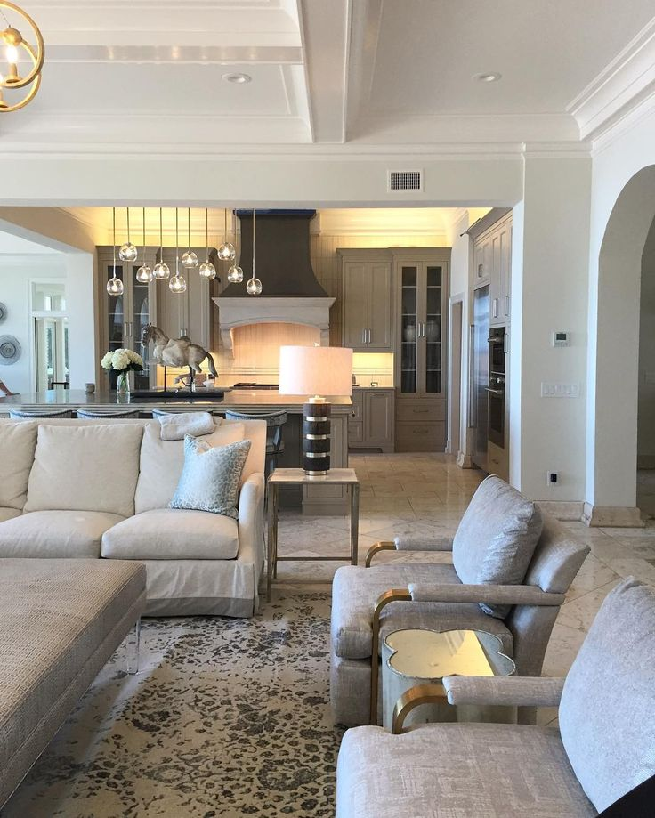 A beautiful neutral color scheme keeps the open concept living room and kitchen easy on the eyes! A mix of metals, kitchen island lighting, and pewter vent hood are the stars!   Lovelace Interiors   Principle Designer Susan Lovelace and Design Associate Brooke Williams