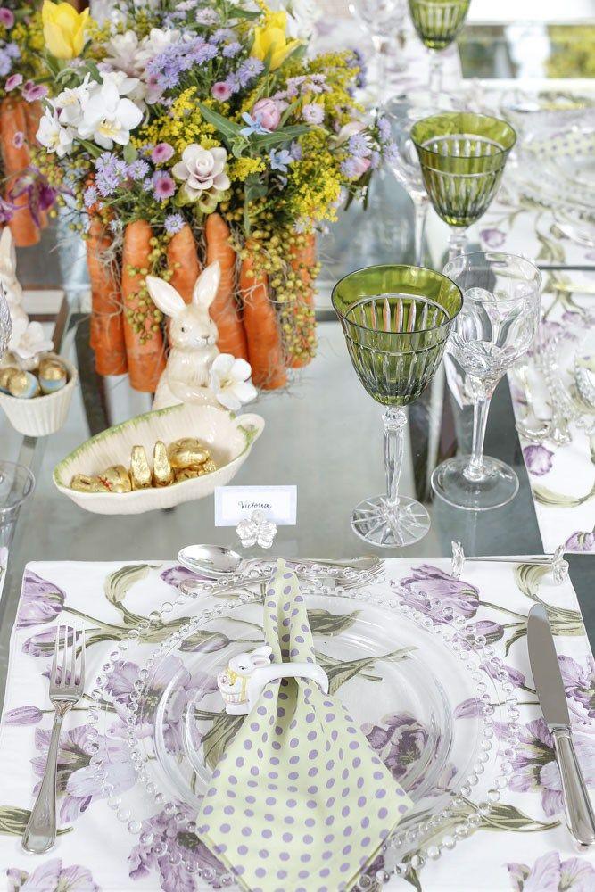 Mesa de Páscoa com Uma mistura de estampas dos jogos americanos de tulipas lilás e dos guardanapos verde com pois lilás e porta-guardanapos de coelho em porcelana tornaram a mesa mais alegre.