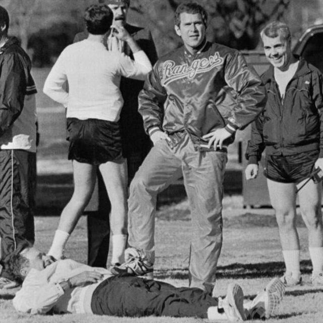George Bush Jr. has a 'leg up' on his father, President George Bush, as the President attempts to stretch prior to jogging at Fort McNair.