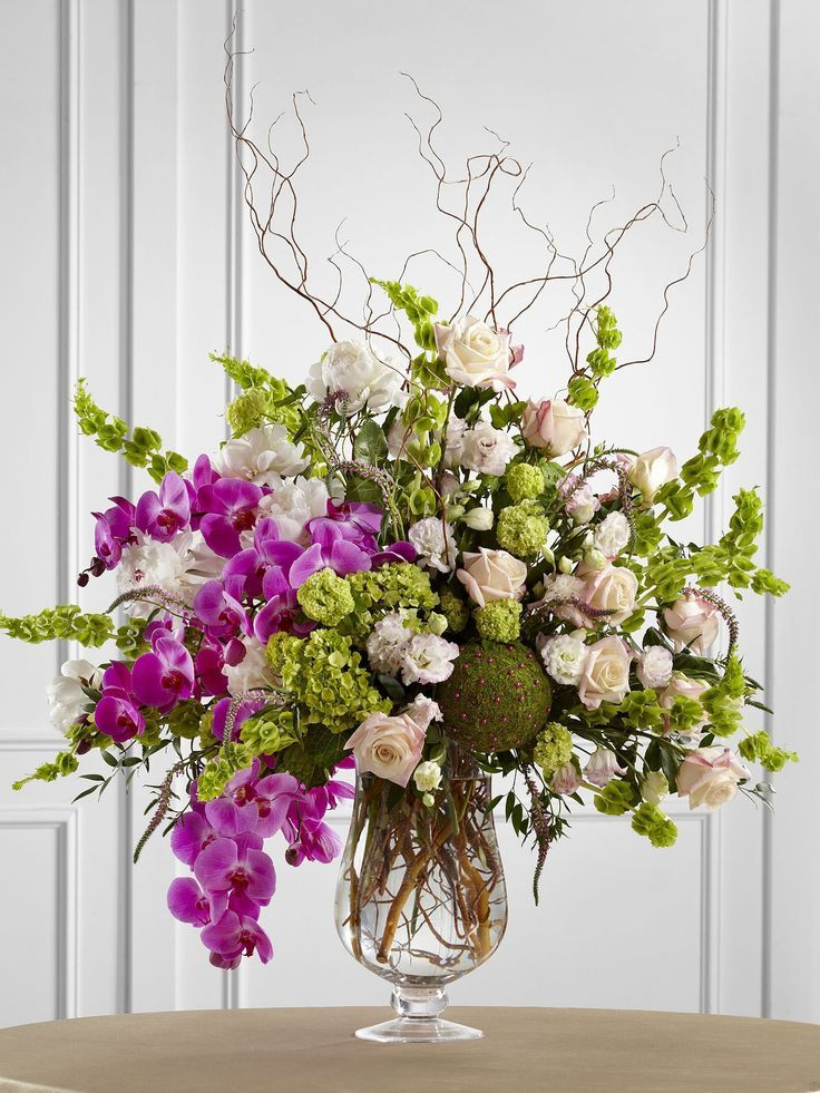 Orchids, roses, hydrangeas and bells of ireland...love the moss sphere studded with pins.