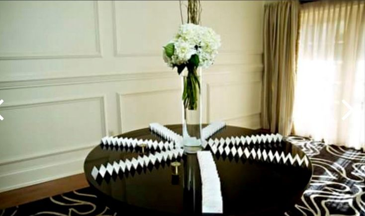 A vase of fluffy white hydrangea with willow on Jen & Chris' escort card table at Cesacphe Ballroom