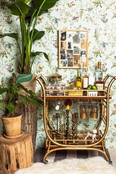 A little old school, a little retro - brass bar cart, candlesticks, gold etched glasses, bird wallpaper
