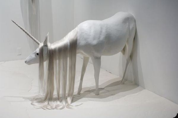 """in medias res, translates from Latin as """"in the middle of things"""", a literary device. In this case, three lifesize unicorns are in the middle of emerging through the walls and melting into the puddle on the floor where already one has appeared to have melted leaving behind only a horn floating on top of the white pool."""