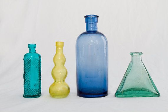 4 colorful glass bottles in different shapes