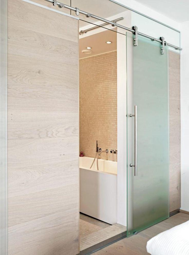 Badet er tilknyttet soverommet, og skilles ved hjelp av en skyvedør i frostet glass.=