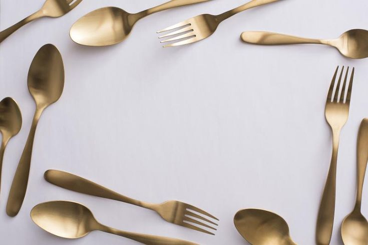 Border of elegant gold cutlery with spoons and forks arranged randomly around central white copy space for food or catering themes - free stock photo from www.freeimages.co.uk