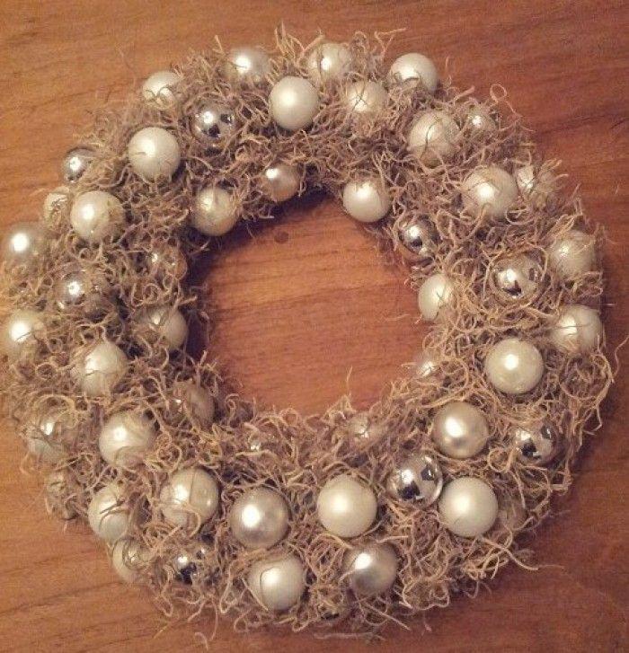 Een mooie krans met kerstballen. De krans is van oase en je drukt de balletjes met lijm in de krans.
