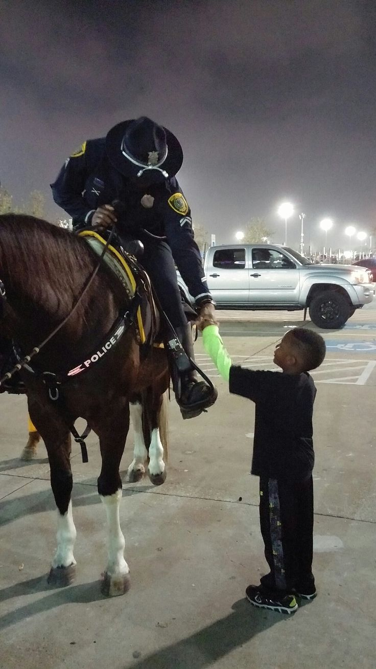 Darrien Phillips Jr., sharing a fist pump with Houston Police Department Mounted Patrol officer E. Bailey at the Houston Livestock Show and Rodeo.