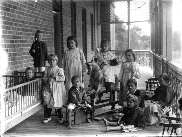 Patients on the verandah of the Royal Children's Hospital, Brisbane, ca. 1899 - Patients pose on the verandah of the Royal Children's Hospital, Brisbane, ca. 1899. The children wear mostly bedclothes. Two boys occupy cots to the left. A girl sits on a rocking horse in the middle of the group. Some children stand and some sit on chairs or on the floor. The brick wall, doorways, windows can be seen on the left and the iron railing of the verandah is visible on the right.
