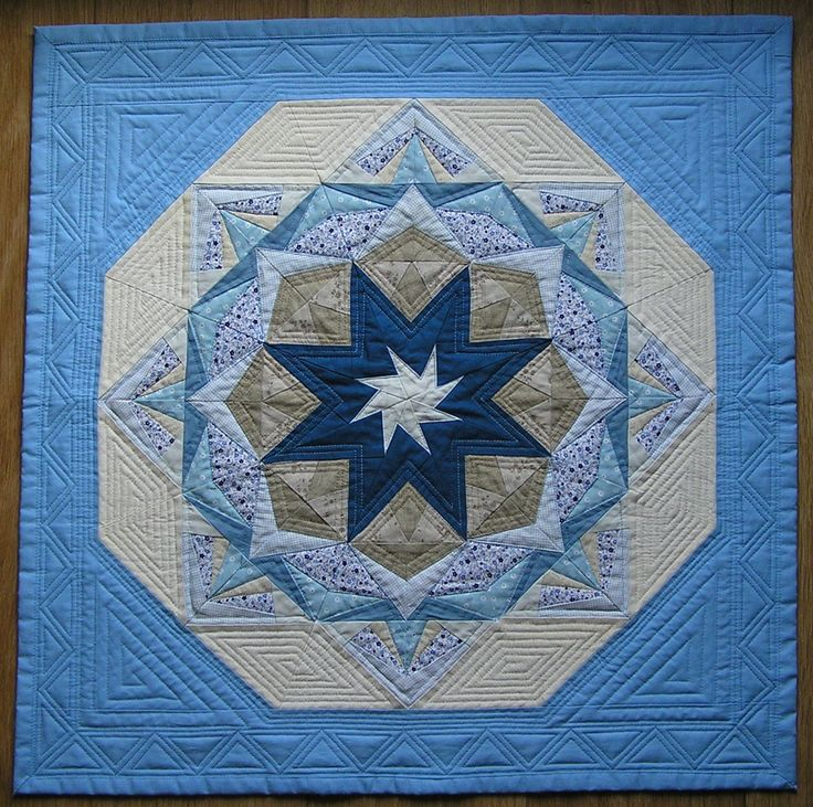 Mandala zpracovaná technikou šití přes papír a bohatě strojově quiltovaná je určena jako dekorace na zeď. Na zadní straně je klasicky opatřena tunelem pro zavěšení. Má rozměry 71,5 x 71,5 cm.
