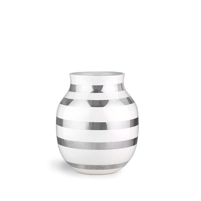 Omaggio Vase Sølv Mellem   Kählers elskede design foreviges i to af tidens hotteste materialer, nemlig metal og keramik. Denne populære vasestørrelse passer perfekt til alle årstiders blomster, og de smukke sølvstriber giver et fantastisk sammenspil med kulørte buketter. Lad den sølvstribede Omaggio-vase i størrelsen mellem skinne om kap med forårssolen og være hjemmets glimtende blikfang.