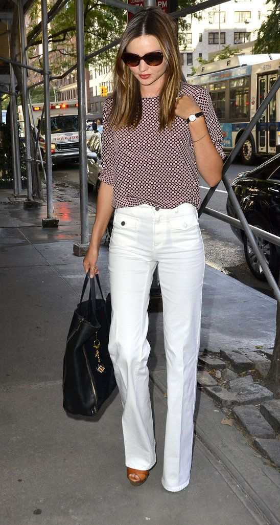 Stylish and crisp: white trousers, satin patterned blouse top, black bag