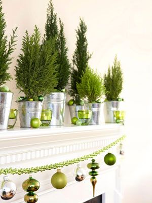 Supermarket spruce seedlings, popped into pails and arrayed along a candlelit mantel, create a wintry woodland scene. Hanging below: a bead garland accessorized with sleek, sculptural ornaments (secured with floral wire). #christmas #holiday #crafts