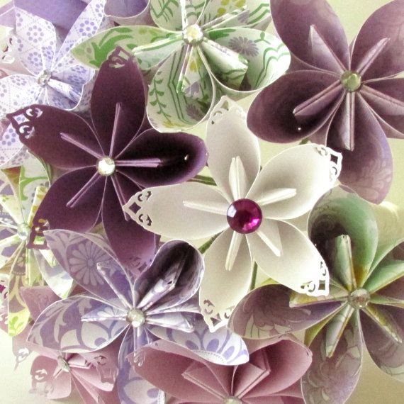 Sixteen origami flowers in shades of purple. Each solid colored paper flower has lace tipped petals. Each petal of every flower is made by hand