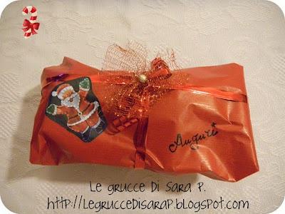 Pacco regalo con fiocco di tessuto a rete e un pallino di polistirolo colorato con spray color oro