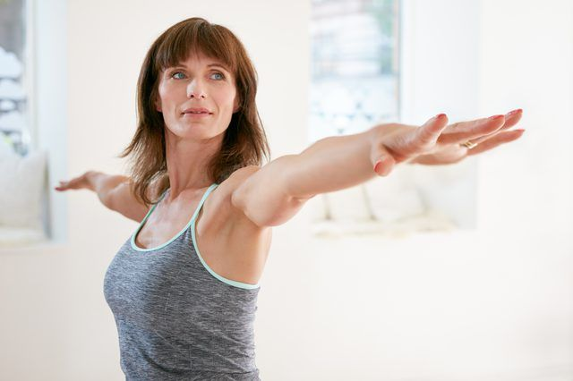 A woman stretches her arms out in a gym.