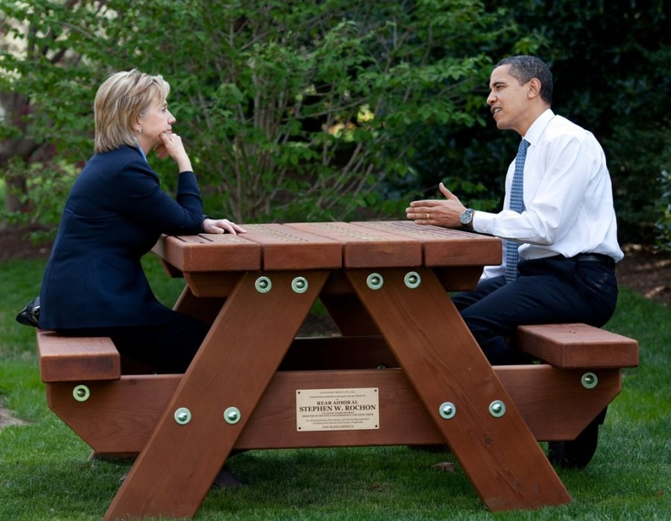 President Barack Obama and Secretary of State Hillary Rodham Clinton speak together sitting at a picnic table April 9, 2009, on the South Lawn of the White House.